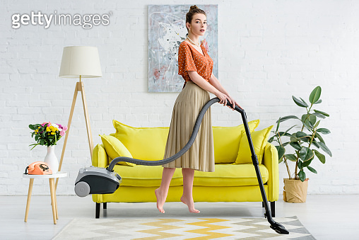 elegant barefoot young woman levitating in air while vacuuming carpet