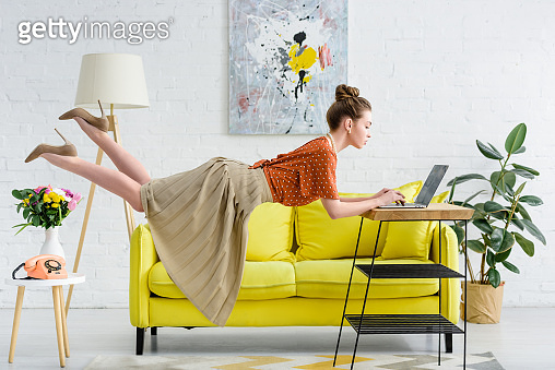 elegant young woman levitating in air and using laptop in living room