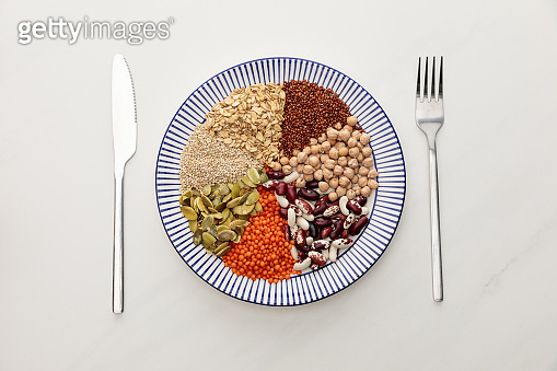 top view of striped plate with raw lentil, chickpea, quinoa, oatmeal, beans and pumpkin seeds near cutlery on marble surface