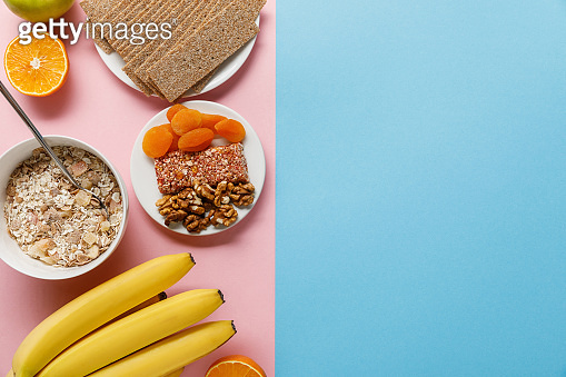 top view of fresh fruits, crispbread and breakfast cereal on blue and pink background with copy space