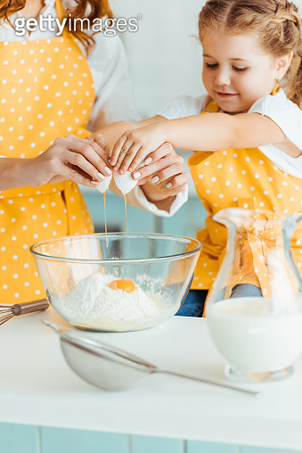 mother and daughter adding smashed egg to flour in bowl while cooking together in kitchen