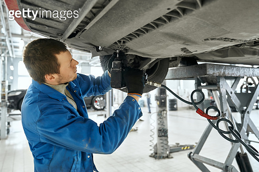 Male specialist repairing the equipment under car in garage