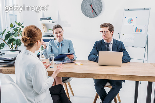 back view of employee talking with recruiters on job interview in office