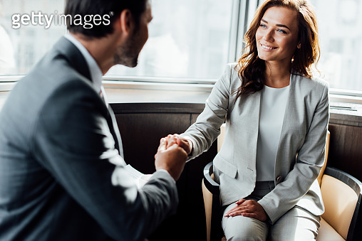 selective focus of happy businesswoman shaking hands with businessman