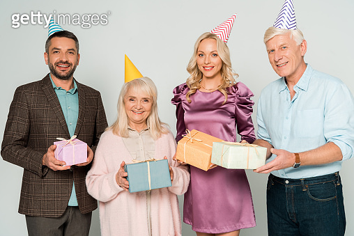 happy senior parents with adult son and daughter holding gift boxes isolated on grey