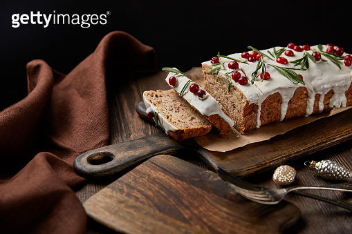 traditional Christmas cake with cranberry near baubles, fork and brown napkin on wooden table isolated on black