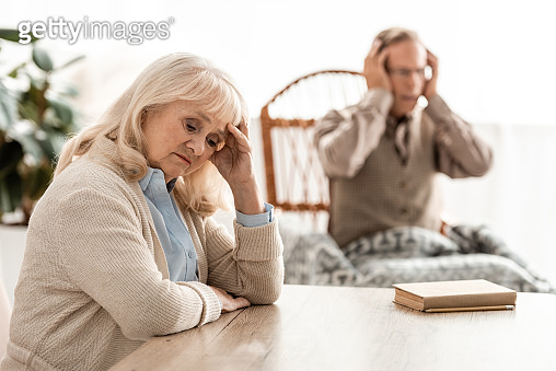 selective focus of upset retired woman sitting near husband with mental illness