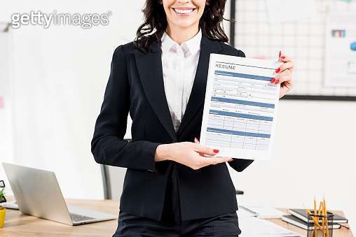 cropped view of cheerful woman holding resume in office