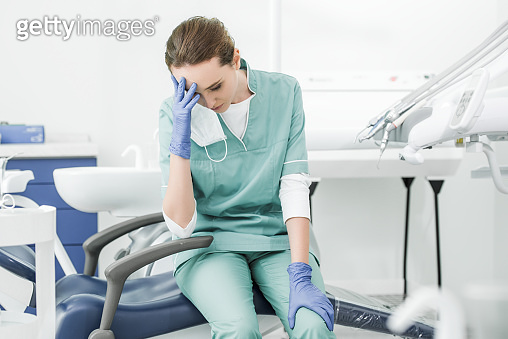 exhausted dentist holding head while sitting on chair in dental clinic