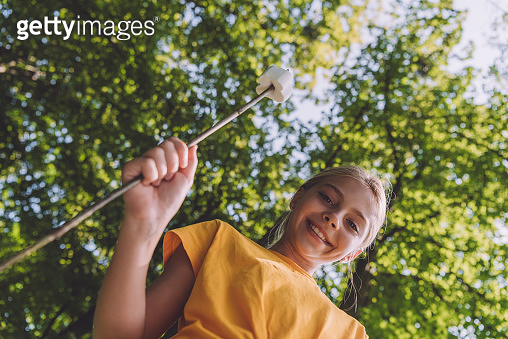 low angle view of happy kid holding sweet marshmallow on stick