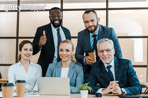 cheerful african american man showing thumb up near coworkers in office