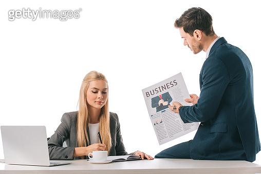 businesswoman writing in notebook while colleague showing business newspaper at workplace with laptop