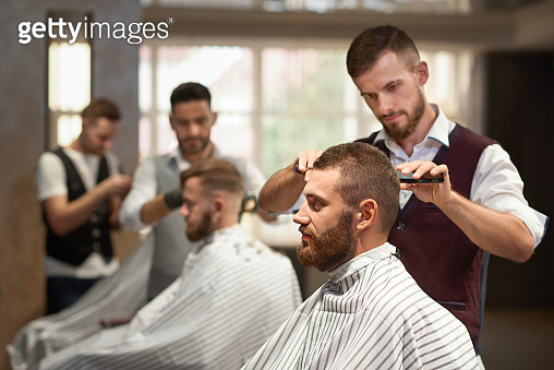 Side view of process of hairstyling in barber shop
