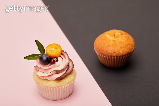 cupcake with cream and cake on pink and black surface