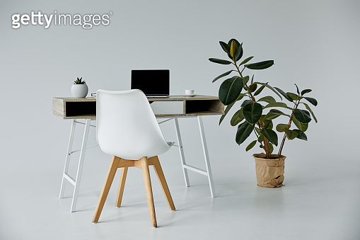 table with laptop, white chair and plants in flowerpots on grey