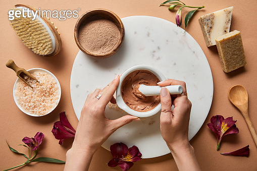 cropped view of woman mixing clay in bowl on marble circle near organic cosmetic ingredients on beige background with scattered flower petals