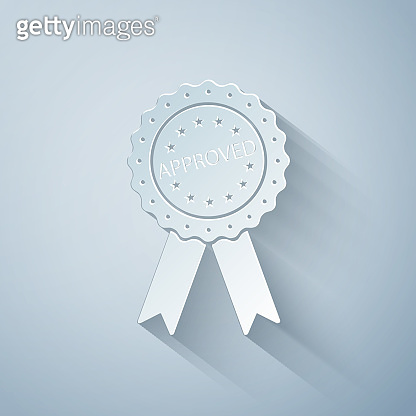 Paper cut Approved or certified medal badge with ribbons icon isolated on grey background. Approved seal stamp sign. Paper art style. Vector Illustration