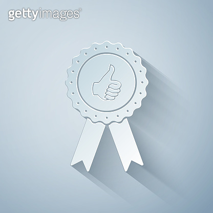 Paper cut Thumbs up on medal badge with ribbons icon isolated on grey background. Paper art style. Vector Illustration