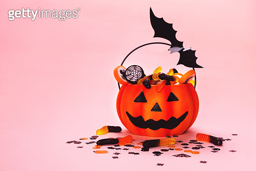 Halloween background made with pumpkin basket, sweets and bat.