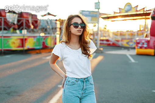 Stylish redhead modern hipster young woman in trendy sunglasses in a white t-shirt in vintage jeans posing on the background of multi-colored rides on a sunny day. Cool girl model for a walk.