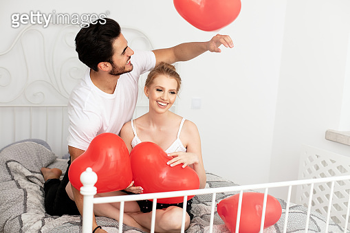Couple posing with red heart balloons.