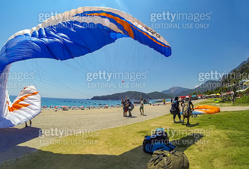 Paragliding in the sky. Paraglider tandem flying over the sea with blue water and mountains in bright sunny day. Blue Lagoon in Oludeniz, Turkey.