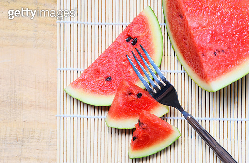 Watermelon slice on wooden plate with a fork fruit summer