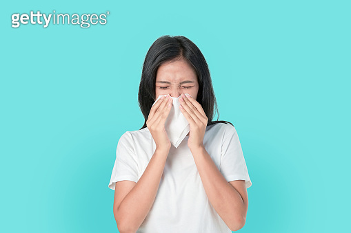 Young Asian woman use paper napkin the mouth and nose because allergy. on the blue background.