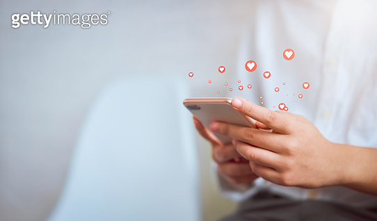 Woman hand using smartphone and show heart icon social media. Concept social network.