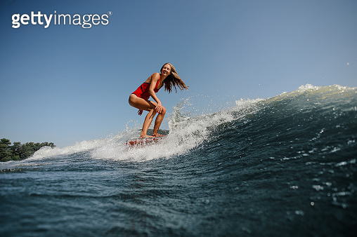 Woman with long hair surfs in sea