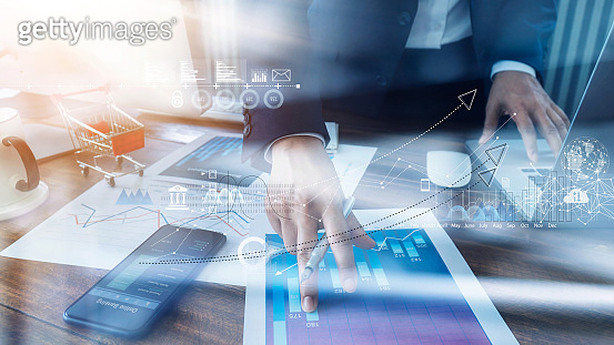 Businessman analyzing sales data and economic growth and pointing at business report document with icon and graph financial, marketing, online banking and payment, business planning and strategy.