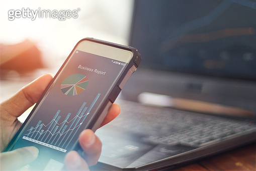 Businessman using mobile smartphone analyzing sales data and economic growth graph chart. Business strategy. business report  Digital marketing.