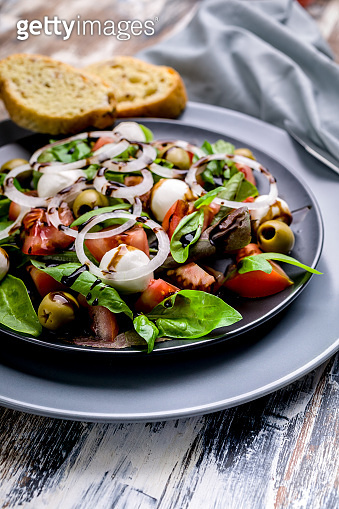 Close up Delicious Mediterranean salad made from fresh herbs with mozzarella, tomatoes, olives, onions and balsamic dressing. Italian traditional cuisine.