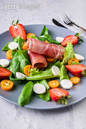 Close up delicious salad with greens, strawberries, beef, lumps and mozzarella. Italian food. Tasty and healthy