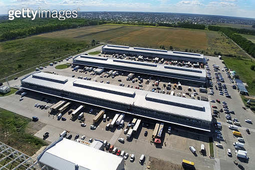 Aerial drone view of group of large modern industrial warehouse or factory buildings in suburban city area.Logistic transportation cargo terminal