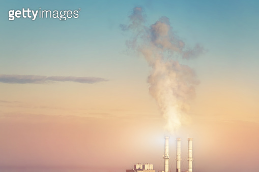 Three smoking stack pipes making clouds of white smoke with dramatic sunset sky background. Industrial minimalistic landscape. Global warming up process and greenhouse effect. Environmental pollution