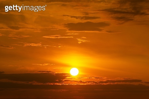 The yellow sun on the orange sky with cloud sunset background
