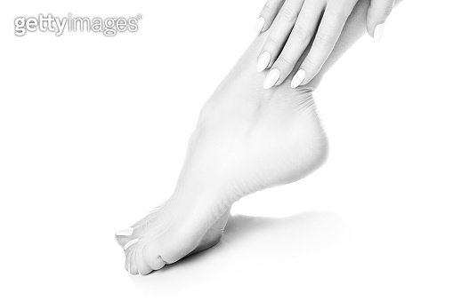 Close-up feet, healthy skin, woman leg barefoot, hand with manicure, pedicure foot. Black and white