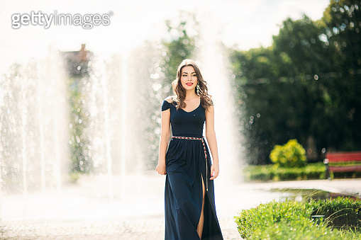 Attractive young model walk in the city. Background of fountain