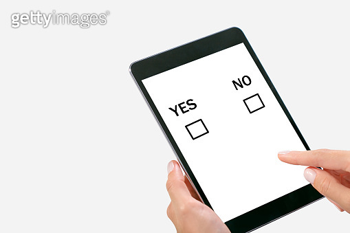 Woman making decision, choosing Yes Or No on the tablet PC.