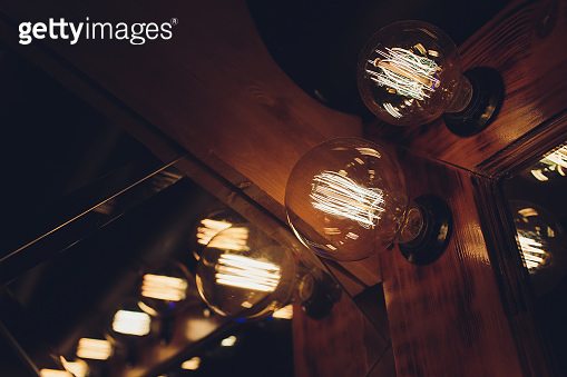 The old edison retro dirty yellow vintage design single tube bulb hanging and glow from ceiling library on night time with copy space using for antique energy electric idea concept decoration.