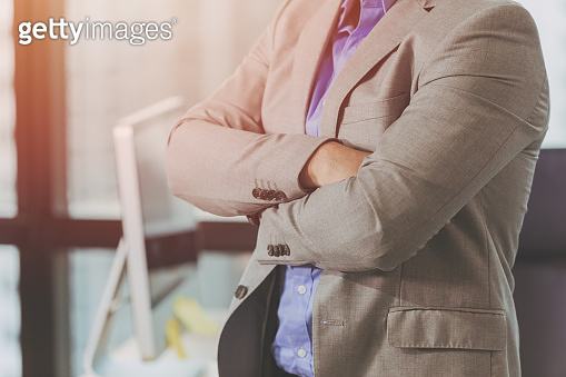 Confident businessman in suit standing with arms folded in business office background