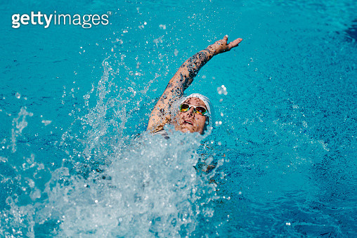 Female with tattoos swimming backstroke