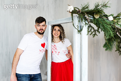 Couple in love standing next to a fir-tree branch on St. Valentine's Day