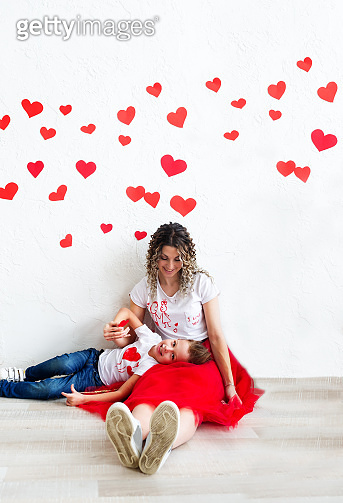 Mom and son sit on the floor against the background of the white wall decorated with red hearts.