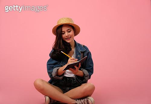 portrait of smiling asian woman wearing jeans jacket writing note. studio shot