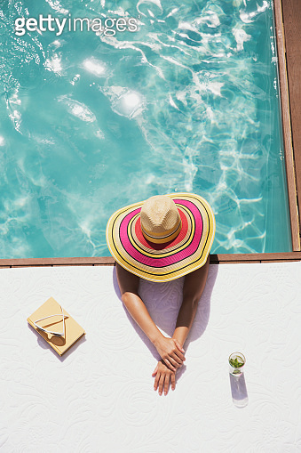 Woman in sun hat in swimming pool