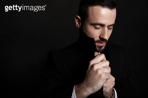 Handsome bearded man wrapping up in black coat. Portrait of a sad guy. Black background.
