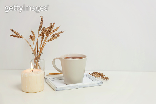 Natural eco home decor with cup coffee and candle on wooden tray