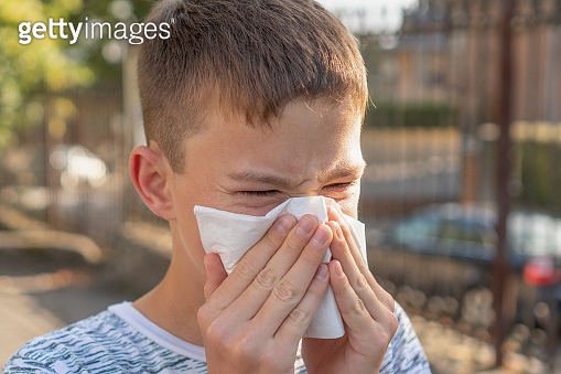 Teen boy blows his nose in a paper handkerchief on a background of trees and cars. Sneezes